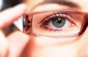 Eye of young woman with eyeglasses. Optometrist concept background